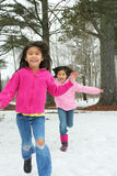 Two girls running through the snow Stock Photo
