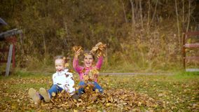 Two girls from running start jump in a heap of autumn leaves. Child playing in autumn garden. Fall foliage. Outdoor fun stock video