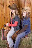 Two girls on saddle with hats Royalty Free Stock Images