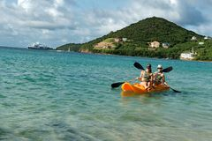Two girls sailing in yellow kayak next to a tropical exotic island. Two girls sailing in yellow kayak next to a tropical exotic island with blue transparent Royalty Free Stock Photography