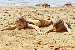 Two girls on sand by the river Royalty Free Stock Photos