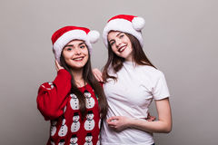 Two girls in Santa hat Stock Photos