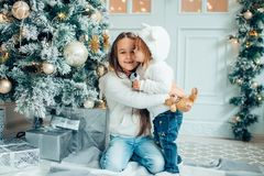 Two Young Girls havung fun In Front Of Christmas Tree. Two girls with santa hat laying in front of the christmas tree Stock Images