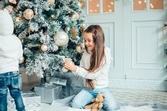 Two Young Girls havung fun In Front Of Christmas Tree. Two girls with santa hat laying in front of the christmas tree Stock Image