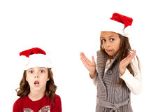 Two girls in santa hats with fun expressions Stock Photo