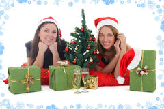 Two girls in santa hats with presents Stock Photos