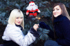 Two girls with Santa and sparklers Stock Photos