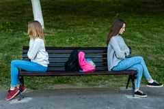 Two girls schoolgirl quarreled in the summer in park. They sit on a bench. The concept of conflict, scandal, problems in royalty free stock photos