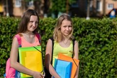 Two girls schoolgirl. Summer in nature. He holds notebooks and textbooks in his hands. Concept Soon to school. Preparation school. Emotion smiles happily. Free stock images