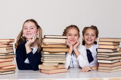 Two girls schoolgirls sit with books at his desk on the lesson at school stock photos