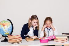 Two girls schoolgirls sitting at his desk on the lesson at school royalty free stock images