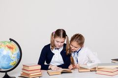Two girls schoolgirls sitting at his desk on the lesson at school stock photography
