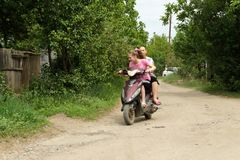 Two girls on a scooter have fun traveling through the village. Kharkiv, Ukraine, may 2013 Stock Photo