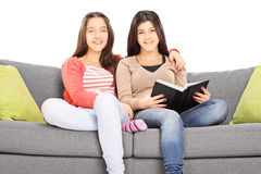 Two girls seated on sofa hugging and looking at camera Royalty Free Stock Image