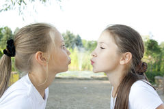 Two girls send air kisses. In the park Royalty Free Stock Photo