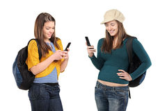 Two girls sending a message by phone. Two beautiful girls sending a message by mobile phone isolated on white background Royalty Free Stock Photography