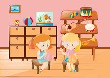 Two girls sewing cloth in the room Stock Image