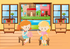 Two girls sewing cloth in room Stock Image