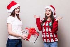 Two girls share Christmas gift box Stock Photos