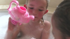 Two Girls Sharing Bubble Bath And Playing With Toy Teapot stock video footage