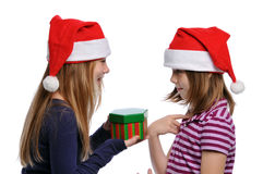 Two girls sharing a Christmas present Stock Images