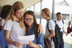 Two girls sharing exam results in school corridor Royalty Free Stock Photo