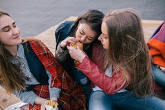 Two girls sharing one burger. Close friendship. Unusual places for rest and communication, spending time together, cheerful and joyful atmosphere concept Stock Images