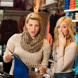 Two girls shocked by a price of clothes in a shop Royalty Free Stock Photo