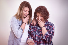Two girls shocked staring at smartphone. Vintage Stock Photography