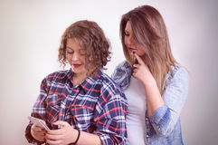 Two girls shocked staring at smartphone. Vintage Royalty Free Stock Photos