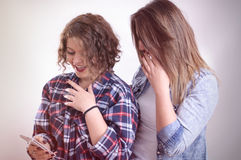 Two girls shocked staring at smartphone. Vintage photo Royalty Free Stock Photos