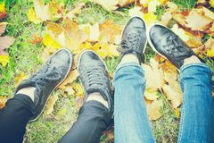 Two girls shoes on autumn leaves, top view, toned photo. Two girls shoes on autumn leaves, top view, sneakers, toned photo Royalty Free Stock Photography