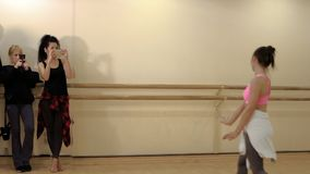 Two girls shoots the dancer on phones. Beautiful brunette performs a sensual dance in the studio. Young woman professionaly moving her body stock video footage