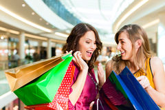 Two girls shopping in mall looking in bags. Two female friends with shopping bags having fun while shopping in a mall Royalty Free Stock Photos