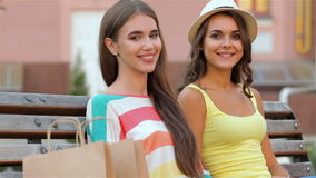 Two girls after shopping sitting on the bench stock footage