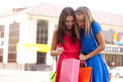 Two girls show each other the purchase Royalty Free Stock Images