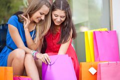 Two girls show each other the purchase Royalty Free Stock Photo