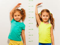 Two girls show height on wall scale at home. Two little girls standing close to the scale on the wall showing height with hand above the head stock images