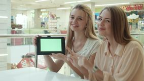 Two girls show the tablet with the green screen. In mall stock footage