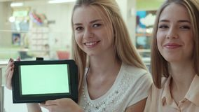 Two girls show the tablet with the green screen. In mall stock video footage