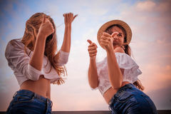 Two girls show thumb up cool Stock Images