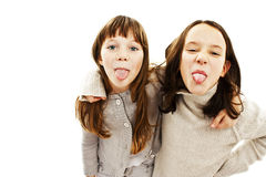 Two girls showing their tongues. Isolated on white background Stock Photography