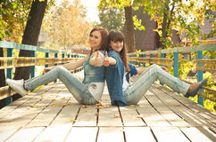 Two girls showing thumbs-up. In autumn leaves outdoors Stock Image