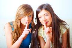 Two girls shushing royalty free stock photography