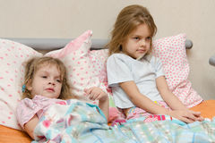 Two girls sick meryat temperature Royalty Free Stock Image