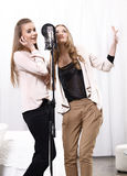 Two girls singing around the microphone in the. Studio Stock Photo