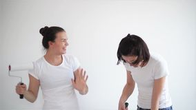 Two girls singing in the paint roller, friends are doing repairs and dancing. HD stock footage