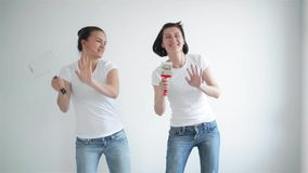 Two girls singing in the paint roller, friends are doing repairs and dancing. HD stock video