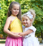 Two girls sister portrait, childhood concept, happy child posing in city park Royalty Free Stock Photos