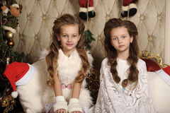 Two girls sisters in a Christmas interior Stock Photos